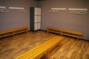 Vista del vestuario femenino, suelo y bancos de madera y taquillas de metal. gimnasio cerca de Cobeña, en Algete