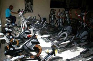 Muchas bicis estáticas libres y un señor pedaleando. Gimnasio Belvis, jarama, fuentelsaz