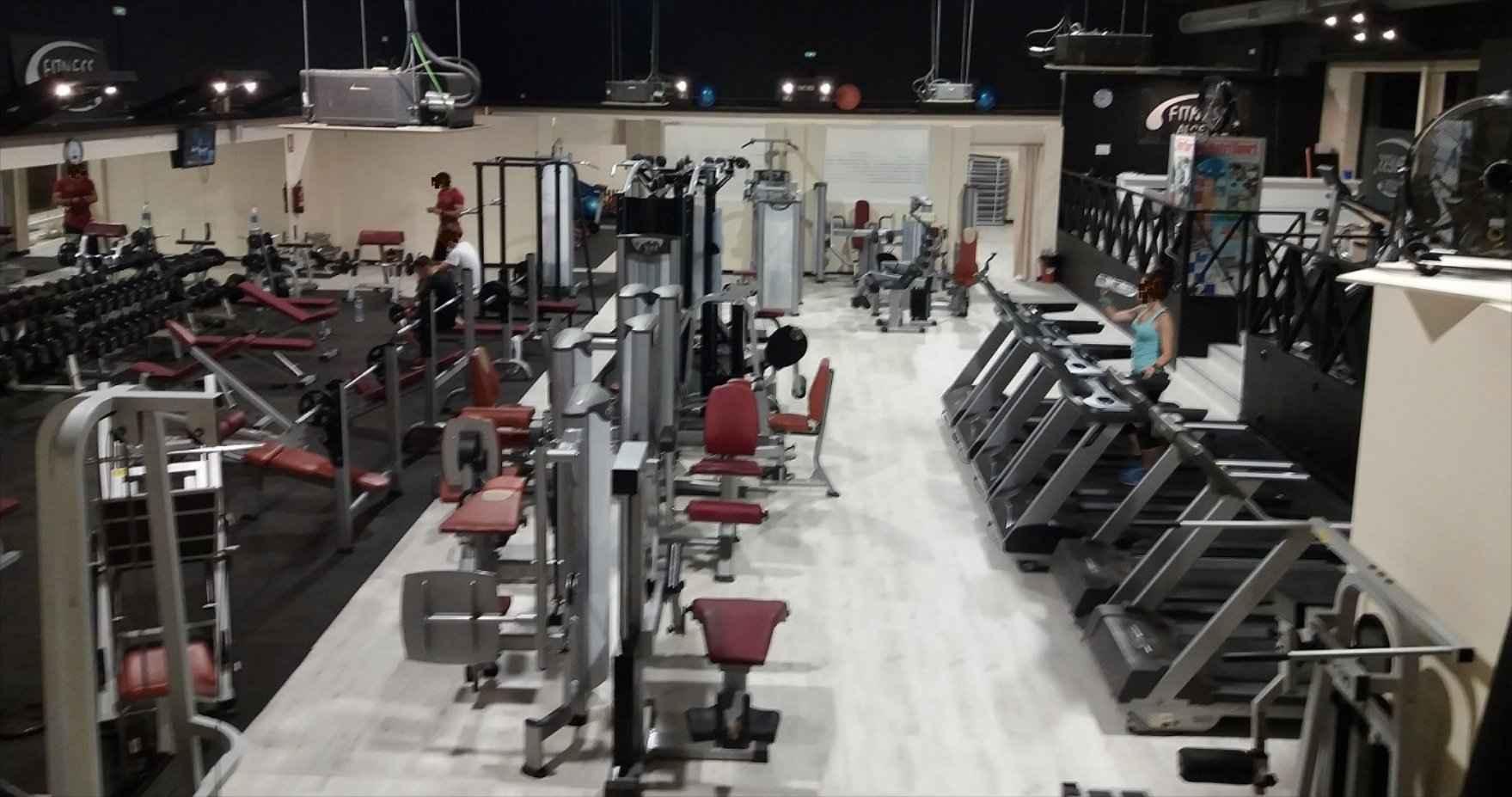 Gente entrenando en sala de musculación y cardio, cinta de andar, pesas, mancuernas.