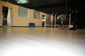 sala con personas haciendo ejercicio en la sala sobre una superficie de tarima clara. Al fondo se ve la sala de boxeo. Zona de Alcobendas. Gimnasio en Algete cerca de Cobeña